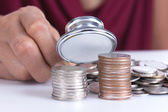 Financial concept, hand hold stethoscope and coins — Stock Photo