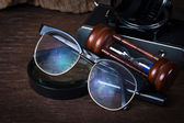 Group of objects on wood table.  glasses, hourglass,old camera, — Stock Photo