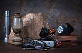 Group of objects on wood table. old clock, old books, rock ,glas — Stock Photo