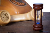 Hourglass and old telephone — Stock Photo
