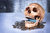 Weathered human skull and coins — Stock Photo