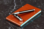 Black pen and notebook — Stock Photo