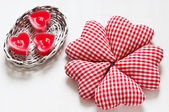 Red valentine's hearts with candes in a white basket — Stock Photo