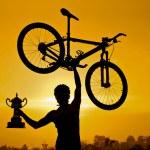 Cyclist raising his mountain bike — Stock Photo