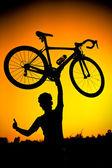 Un ciclista levantando su bicicleta — Foto de Stock