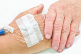 Old hands holding each other with IV solution in a patient's hand — Stock Photo