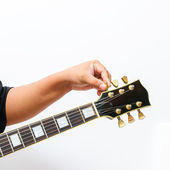 Hand tuning the electric guitar — Stock Photo