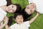 Family lying on the grass — Stock Photo