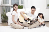 Young family playing guitar — Stock Photo