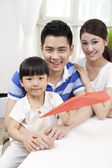 Family palying paper airplane — Stock Photo