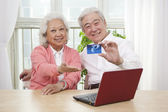 Senior couple holding credit card — Stock Photo