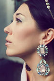 Portrait of beautiful young woman with tiara and earrings. — Stock Photo