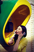 Girl in a yellow shirt in a call-box — Stock Photo