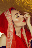 Arabic young woman. Gold makeup. Red clothes. — Stock Photo