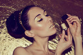 Portrait of young woman with gold makeup — Стоковое фото