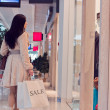 Stock Photo: Girl in shopping centre with shopping bags