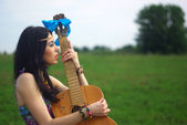 Portrait of hippie posing outdoor with guitar — Stock Photo