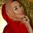 Stock Photo: Arabic young woman. Gold makeup. Red clothes.