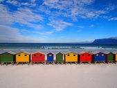 Row of wooden brightly colored huts — Stock Photo
