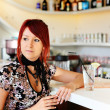 Girl sitting at the bar counter — Stok fotoğraf