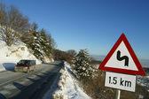 Road through snowy forest — ストック写真