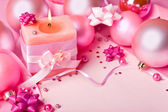 Candle and New Year's spheres in pink tones — Stock Photo