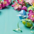 Colored Easter eggs with ribbons and flowers on a turquoise tabl — Stock Photo #37414643