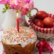 Easter cake with a lit candle, jug with flowers and painted eggs — Stock Photo #39020755
