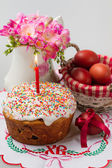 Easter cake with a lit candle, jug with flowers and painted eggs — Stock Photo