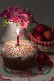 Easter cake with a lit candle, flowers and painted eggs — Stock Photo