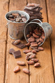 Cocoa beans in two tin buckets and dark chocolate — Stock Photo