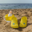 Yellow slippers, bucket and cream on the beach — Stock Photo