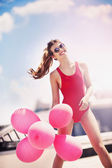 Beautiful happy girl with red balloons on the roof — Stock Photo