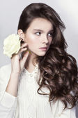 Beautiful portrait of young girl with long curly hair and white rose — Stock Photo