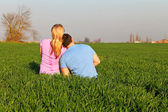 Girl with a guy in a field — Stock Photo