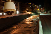 CCTV Camera Operating on road with canal in city at night — Stockfoto