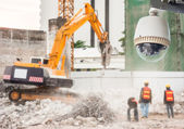 CCTV camera watching an excavator and workers working on a construction site — Stock Photo