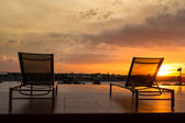 Swimming pool chair by swimming pool with sunset — Stock Photo