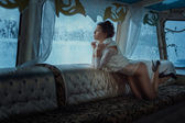 Girl looks in the winter window. — Stock Photo