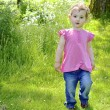 Young girl walking outside. A pretty young child, toddler wearing pink top and blue jeans as she walks through a park or meadow. — Stock Photo