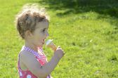 Pretty young girl eating ice cream. She is wearing a pink and white dress, with the sun behind her (backlit). She has blonde curly hair and is looking towards the camera. — Stockfoto