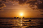 Sailingboats and silhouette of couple against a beautiful sunset — Stockfoto