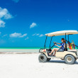 Young woman driving golf cart along tropical white beach in Caribbean vacation — Stock Photo #50260283