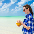 Young woman drinking coconut water against the background of turquoise sea at tropical beach during Caribbean vacation — Stok fotoğraf #50260349