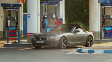 Blonde in elite car at a gas station — Stock Video