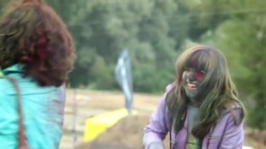 Smiling laughing adult girls toss paint at each other happiness — Stock Video