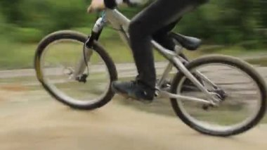 Bicycle rider BMX races difficult track, spinning wheels daytime — Stock Video