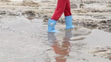 Child feet walk on puddle dirt — Stock Video