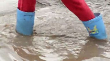 Child feet in rubber boots walk puddle dirt — Stock Video
