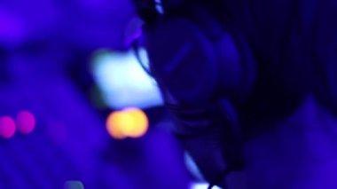 DJ in headphones behind the deck — Stock Video